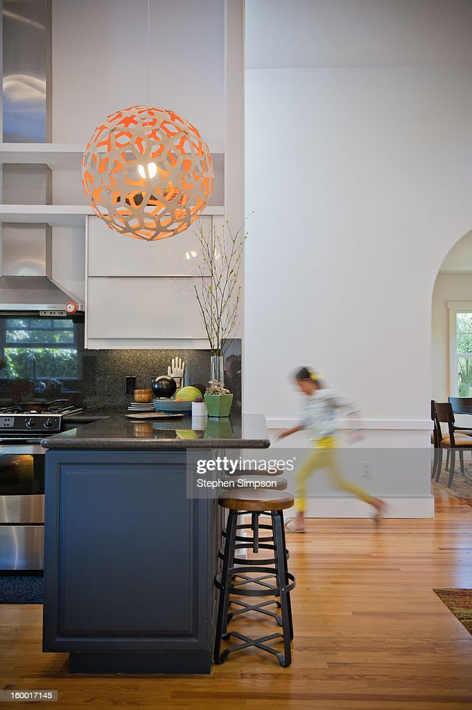 girl rushes by empty kitchen area : Stock Photo