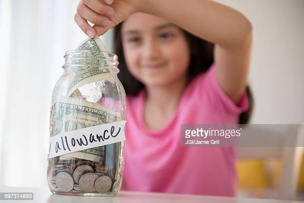 Girl saving allowance in money jar