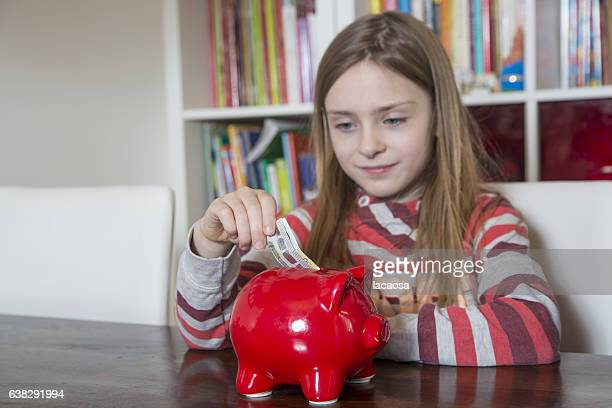 Girl saving money in red piggy bank