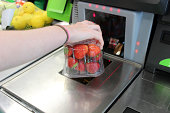 Photo showing a girl scanning her shopping (including fresh fruit / organic strawberries) at a self-service supermarket checkout till (also known as 'Self Checkouts' and 'Semi Attended Customer Activa