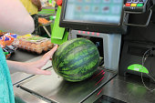 Photo showing a girl scanning her shopping (including a large green watermelon) at a self-service supermarket checkout till (also known as 'Self Checkouts' and 'Semi Attended Customer Activated Termin