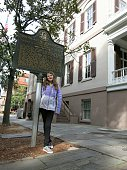 Girl Scout, age 10 or 11 stands below historical marker sign in front of the birthplace house of Girl Scout founder, Juliet Lowe, in Savannah, Georgia.