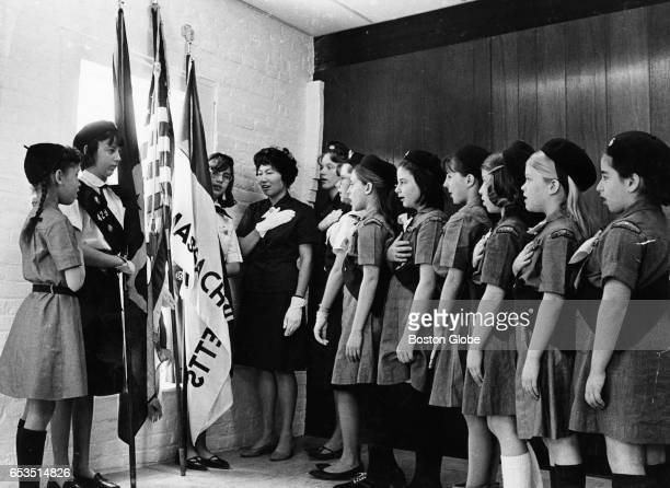 Girl Scouts participate in the flag ceremony at the new Bay Path Colonial Council offices at 381 Elliot St in Newton Mass April 1964 From left are...