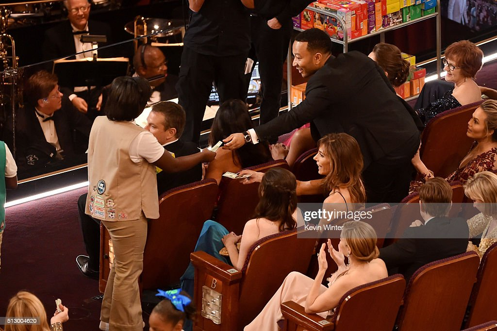 Girl Scouts sell cookies to audience members including musician John Legend (R) during the 88th Annual Academy Awards at the Dolby Theatre on February 28, 2016 in Hollywood, California.