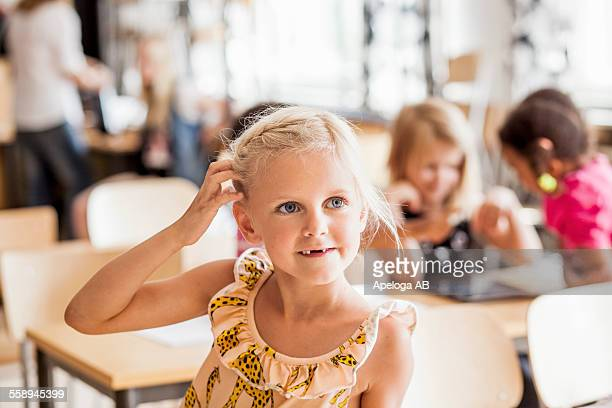Girl scratching head while looking away in classroom