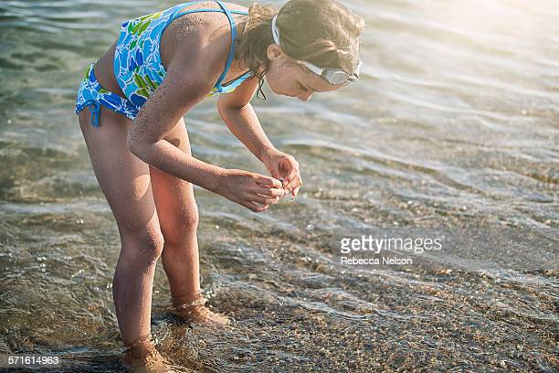 girl searching for rocks in lake
