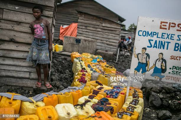 A girl secures the family's water containers with a piece of cloth as other residents also lined up their containers to the water stand in Majengo...