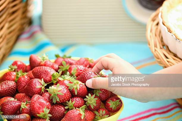Girl (7-9) selecting strawberry from bowl, close-up