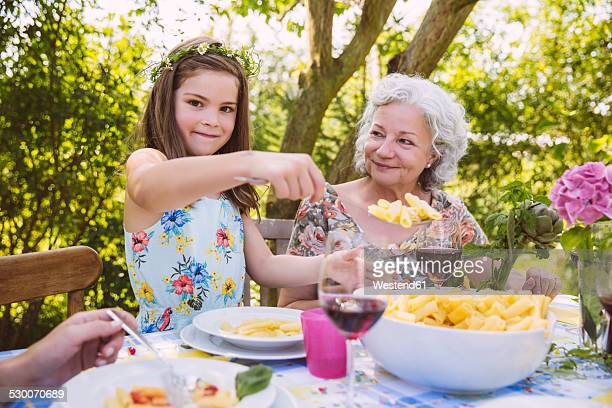 Girl serving pasta to grandmother at garden party