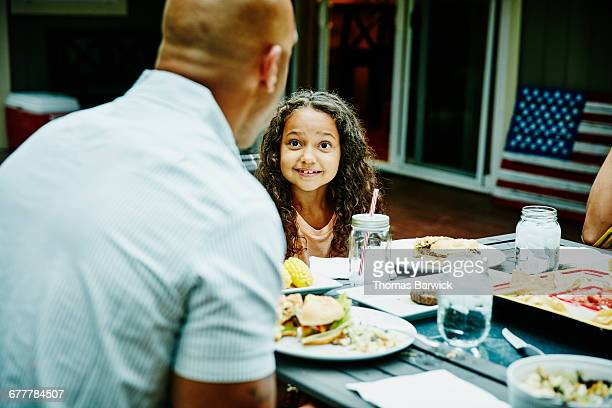 Girl sharing dinner with family in backyard