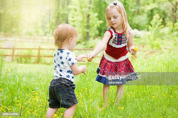 Ragazza condivisione fiori con piccolo fratello