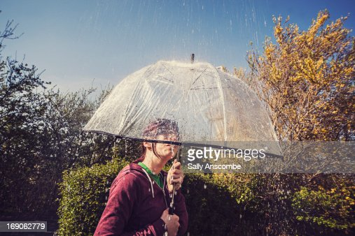 Girl sheltering under an umbrella