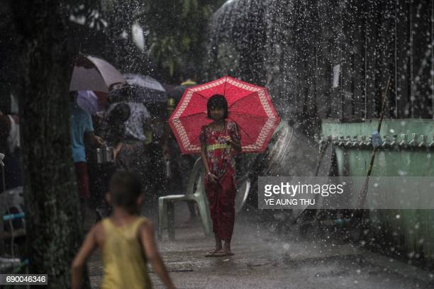 TOPSHOT A girl shields herself from the rain with an umbrella as it rains in Yangon on May 30 2017 Tropical Cyclone Mora which formed in the Bay of...