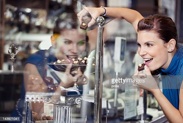 girl shopping and admireing  different chocolate goodies through shop window