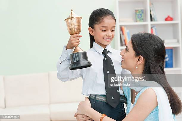 Girl showing a trophy to her mother