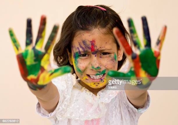 Girl showing colorful painted hands