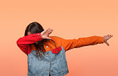 Anonymous girl in colorful denim jacket standing in dab dance pose on orange background.