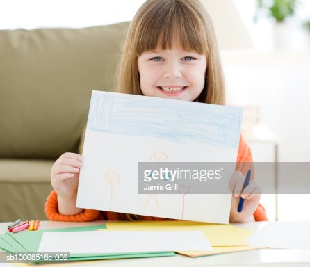 Girl (6-7) showing drawing, smiling, portrait : Stock Photo
