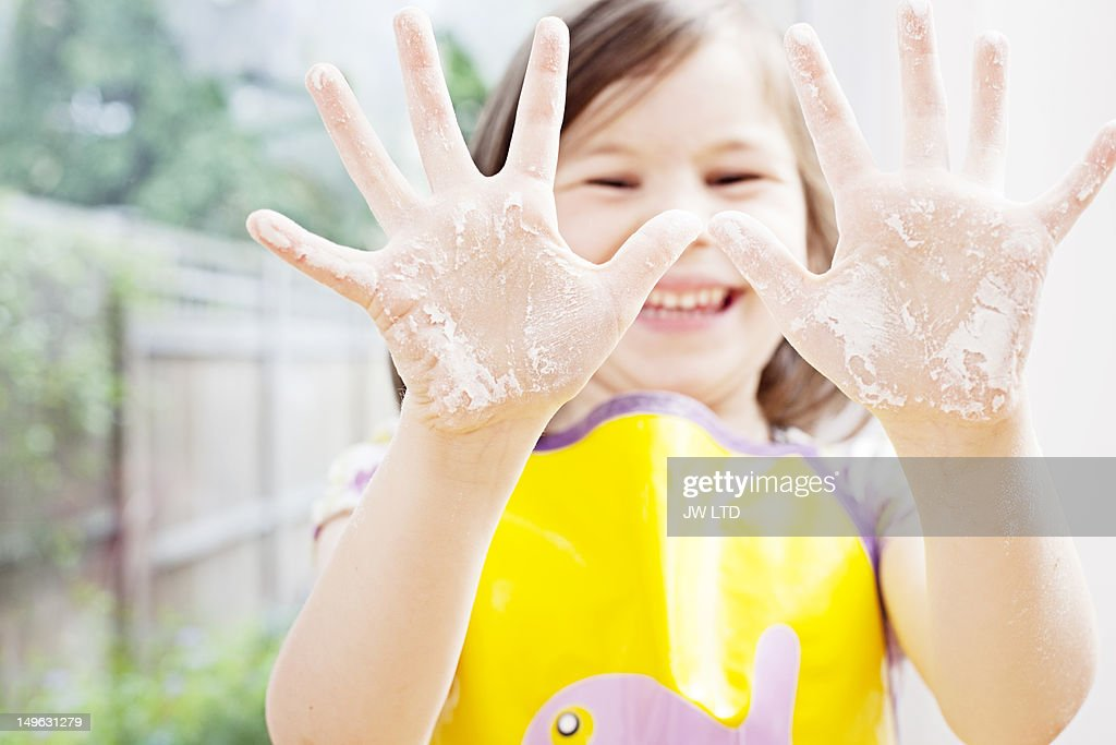 Girl (4-5) showing her hands covered with flour : Stock Photo