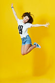 Cheerful hipster girl jumpig with hands spread wide over yellow background. Young woman in jump.