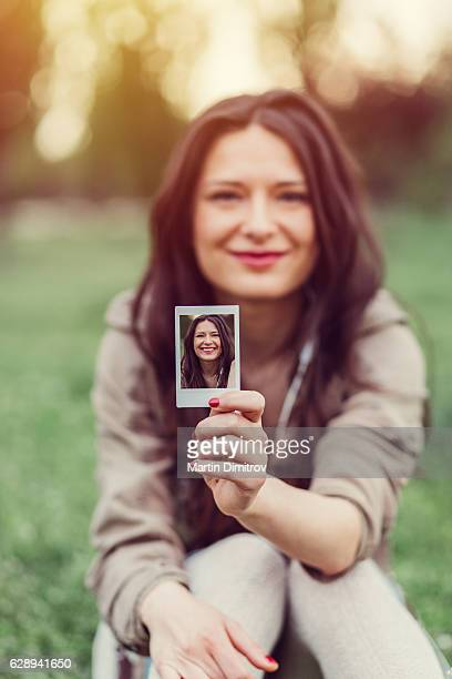 Girl showing his own photo to the camera
