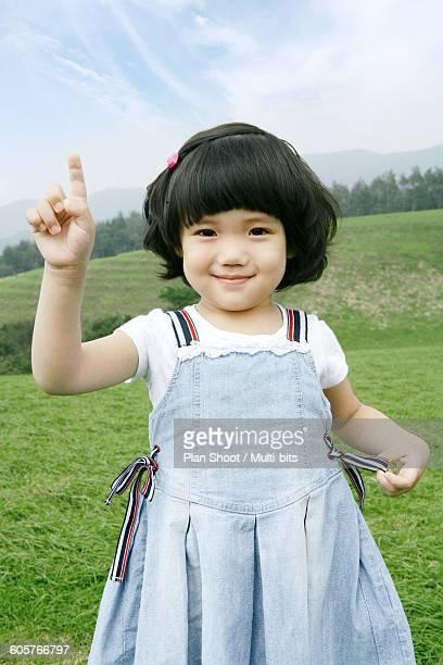 Girl (4-5) showing index finger, smiling, portrait, close-up
