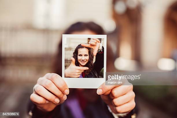 Girl showing instant photo of hand framing concept