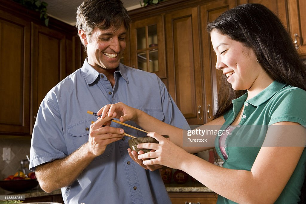 girl showing man how to use chopsticks : Stock Photo