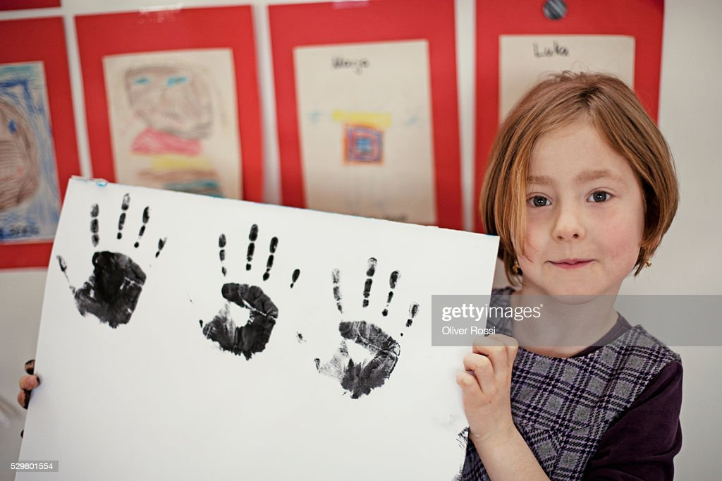Girl (6-7) showing multiple hand prints : Stock Photo