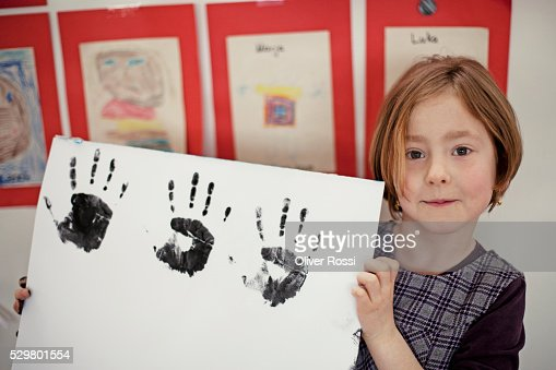 Girl (6-7) showing multiple hand prints : Stock-Foto