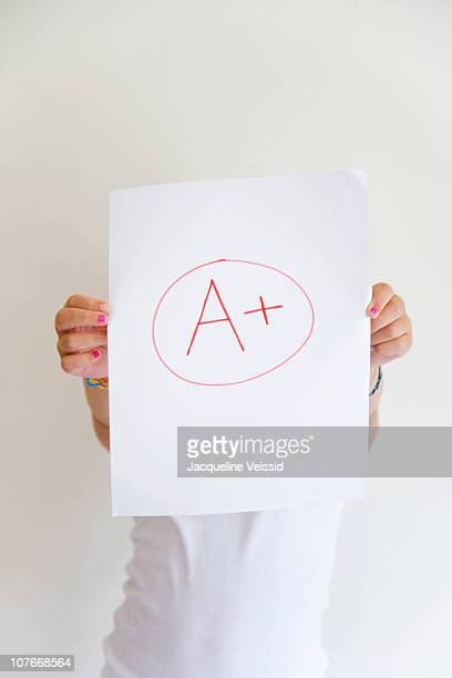Girl showing off A+ grade on paper