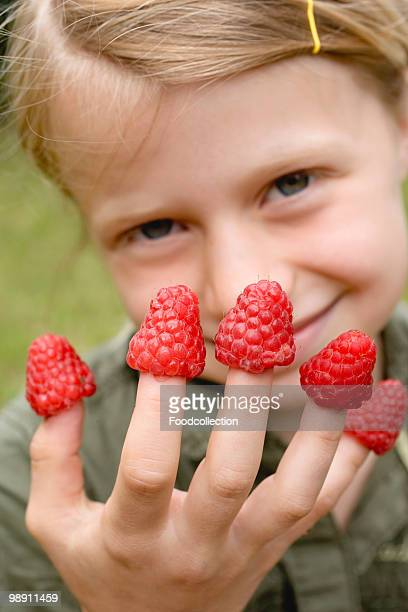 Girl (6-7) showing raspberries on fingers, smiling, close-up