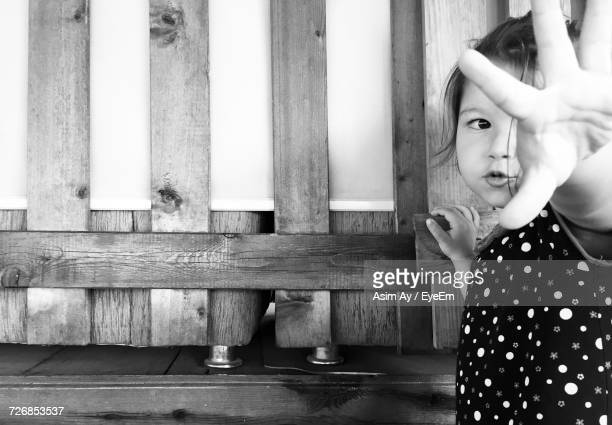 Girl Showing Stop Gesture By Wooden Railing