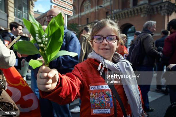 A girl shows lilys of the valley More than 10 000 people took to the streets for the rally of May Day in Toulouse France on 1st May 2017 This year...