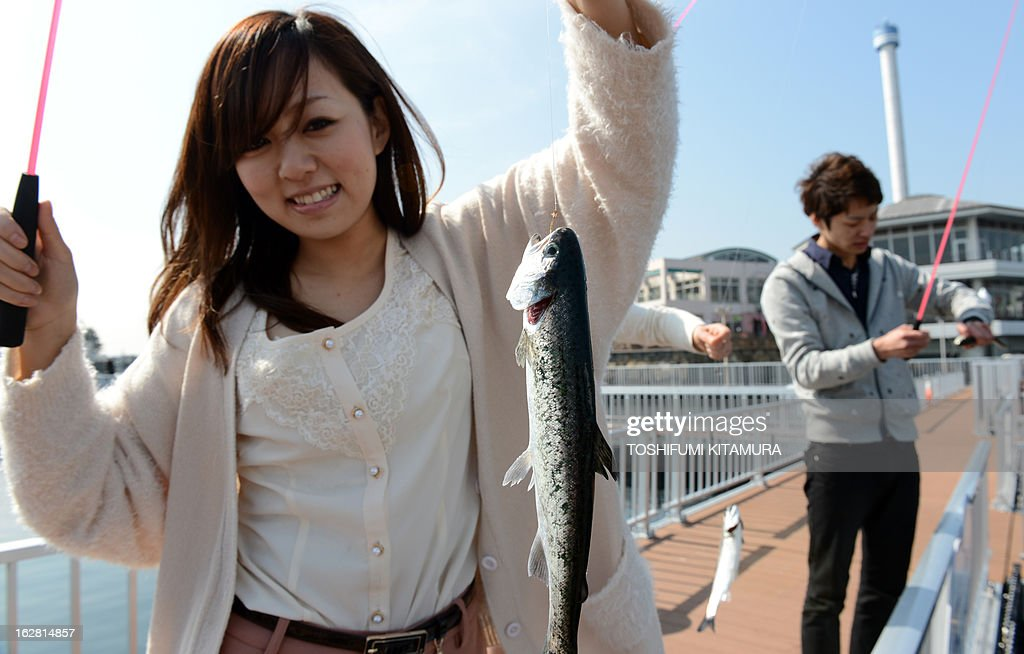 A girl shows off a fish caught during a press preview of Yokohama Hakkeijima SeaParadise's new attraction facilities, 'Umi Farm,' or Sea Farm in Yokohama on February 28, 2013. The 'Umi Farm' opens on March 8 and will teach children about the ocean's ecological nature as well as fishing or hunting fish. AFP PHOTO / TOSHIFUMI KITAMURA