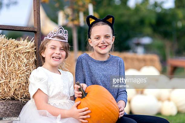 Girl siblings wearing halloween cosstumes together holding a pumpkin