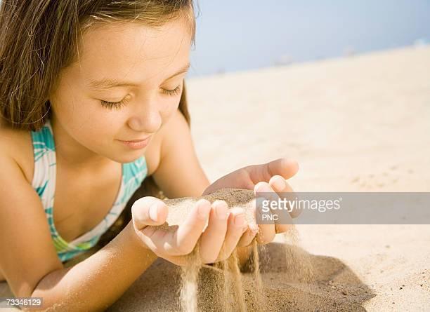 Girl (7-9) sifting sand on beach