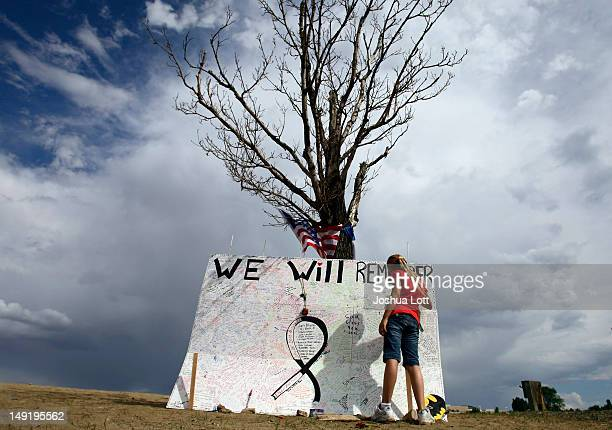 A girl signs a message board at a memorial across the street from the Century 16 movie theatre July 24 2012 in Aurora Colorado The memorial was...