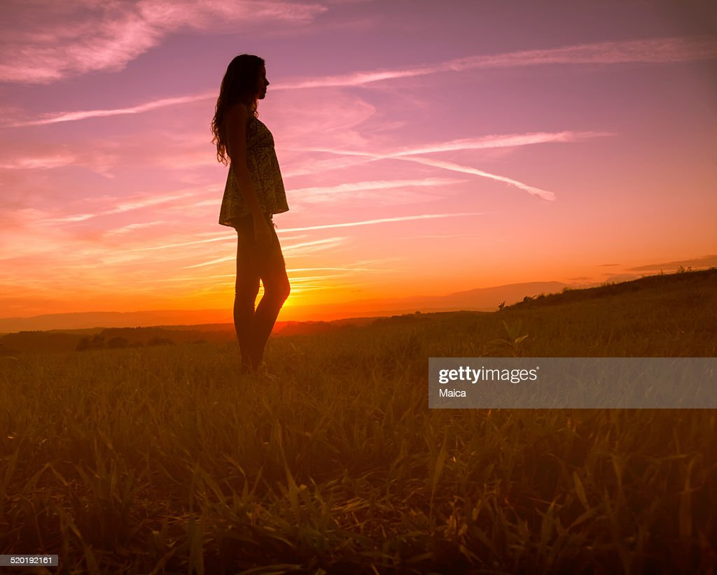 Girl silhouette in a sunse beautiful landscape