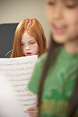 Girl (6-12) singing from music sheet in class (Focus on girl)
