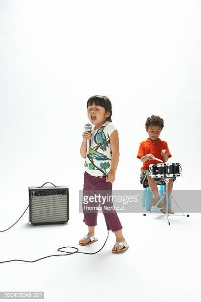Girl (4-6) singing into microphone while boy (4-6) plays drum