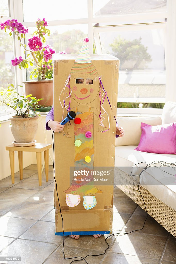 Girl singing karaoke covered in decorated box. : Stock Photo