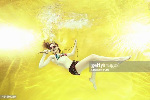 Girl singing underwater on yellow background