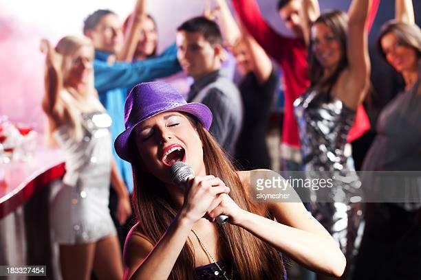 Girl signos de una canción en el medio ambiente de sus amigos.