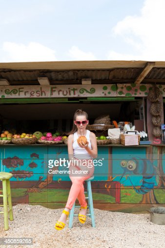 Girl sipping coconut at fruit stand : Stock Photo