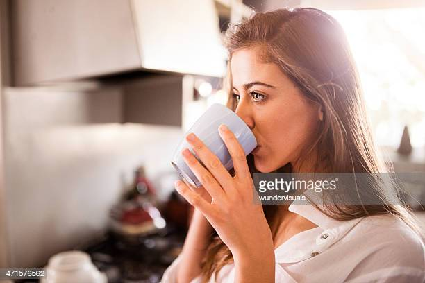 Girl sipping her morning coffee in her kitchen