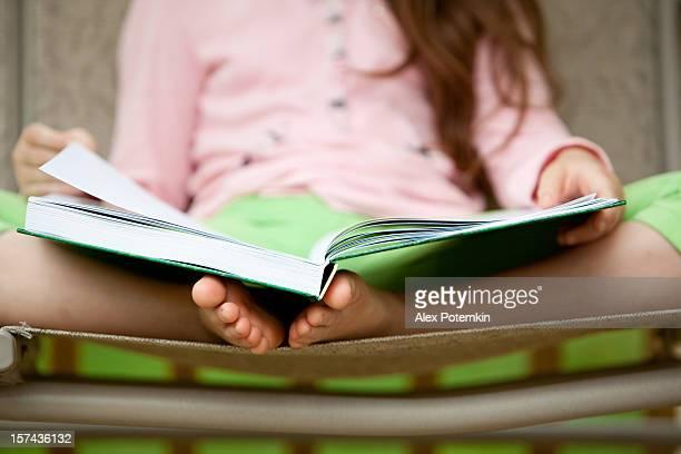Fille assis sur la Balançoire à bascule et lire le livre