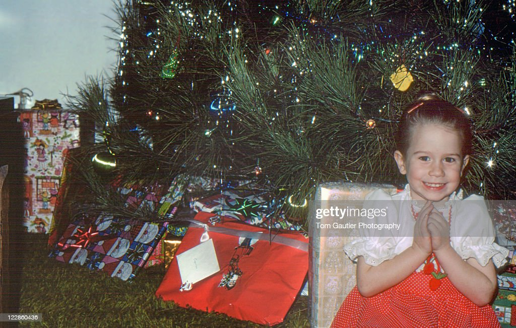 Girl siting in front of Christmas tree : Stock Photo