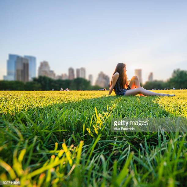 Girl siting in front of Manhattan skyline in Central Park