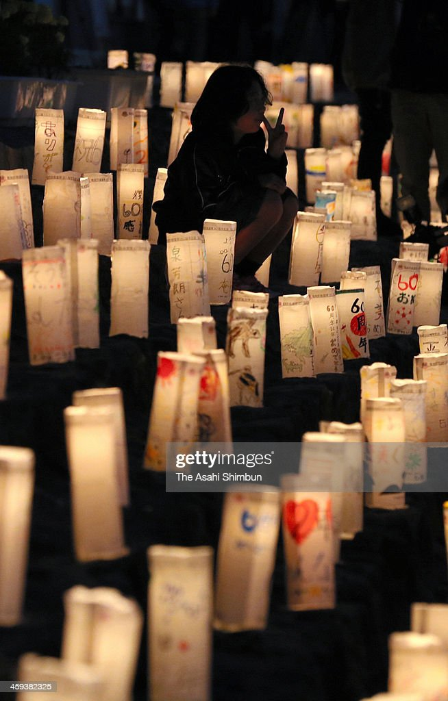 A girl sits among candle-lit paper lanterns placed to celebrate the 60th anniversary of the Amami Oshima islands' reversion to Japanese administration on December 25, 2013 in Amami, Kagoshima, Japan. Amami islands, located between Kyushu island and Okinawa, is reversed to Japan in 1953 from the United States.